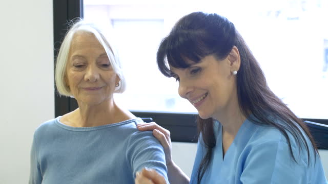 nurse assisting senior woman with hand exercise - fisioterapia video stock e b–roll