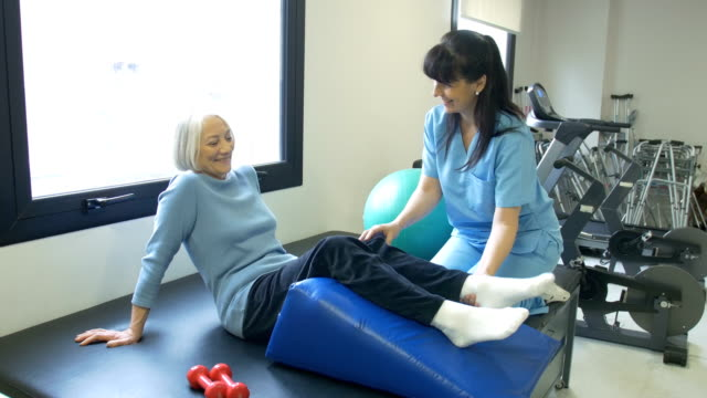 nurse assisting senior woman with leg exercise - fisioterapia video stock e b–roll