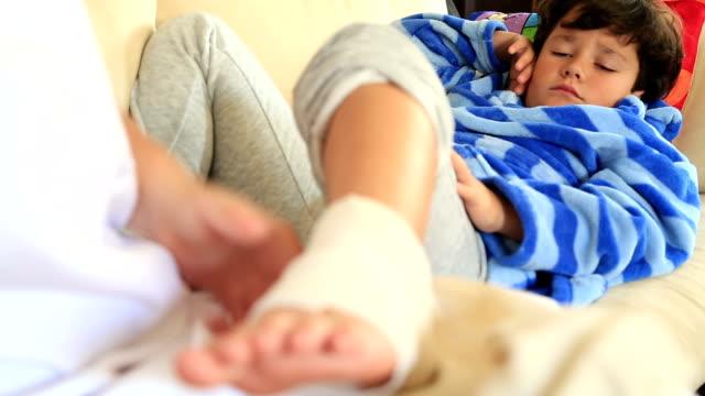 Nurse bandaging little boy ankle video