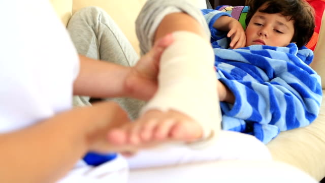Nurse bandaging little boy ankle Doctor/nurse hands bandaging a child's sprained ankle. ankle stock videos & royalty-free footage