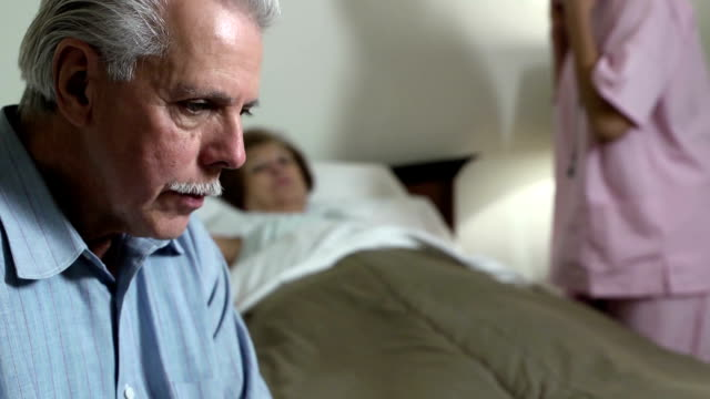 Nurse Cares for Sick Latin Woman Close up of senior Latin man expressing concern for senior Latin Woman.  Nurse in background. cancer patient stock videos & royalty-free footage