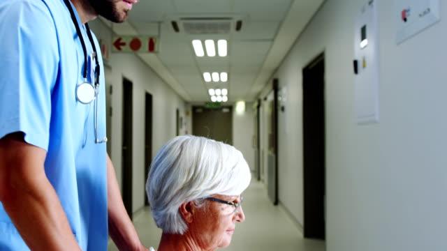 vidéos et rushes de l'infirmière comptable patiente senior avec chaise roulante - infirmier