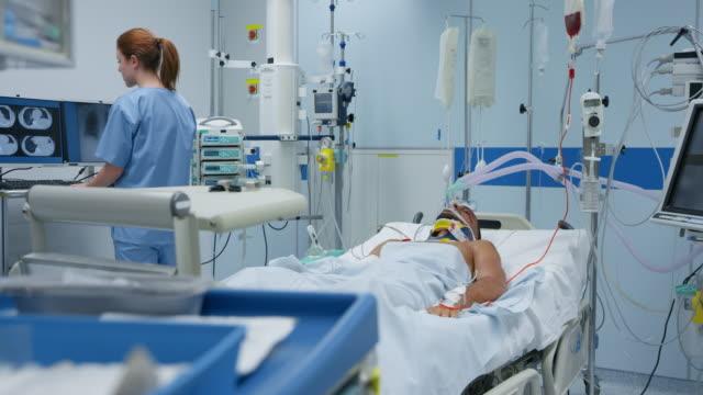 ds sjuksköterska kontrollera en ung manlig patient i intensivvården - intensivvårdsavdelning bildbanksvideor och videomaterial från bakom kulisserna