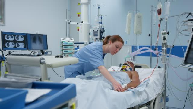 icu krankenschwester überprüfung junge männliche patienten mit technischer belüftung - krankenstation stock-videos und b-roll-filmmaterial