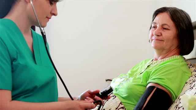 Nurse checking blood pressure to senior woman video
