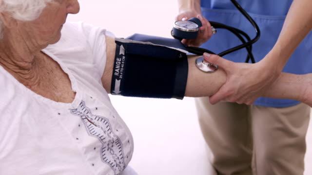 Nurse checking bloody pressure of senior woman video