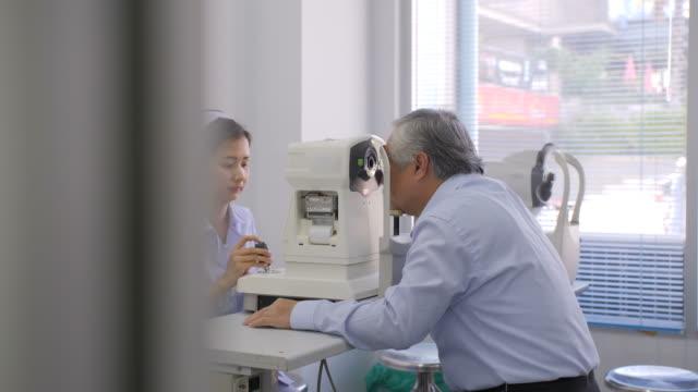 vidéos et rushes de infirmière, vérification des yeux de patients âgés avec dispositif médical biomicroscope - rétine