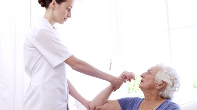 infermiera controllo senior womans braccio - fragilità video stock e b–roll