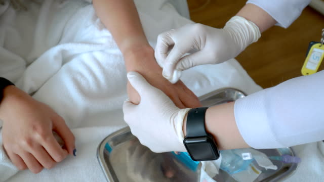nurse cleaning patient's back of hand - rana filmów i materiałów b-roll