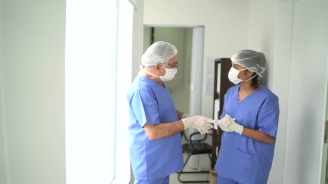 Nurse colleagues talking at corridor before an surgery on hospital