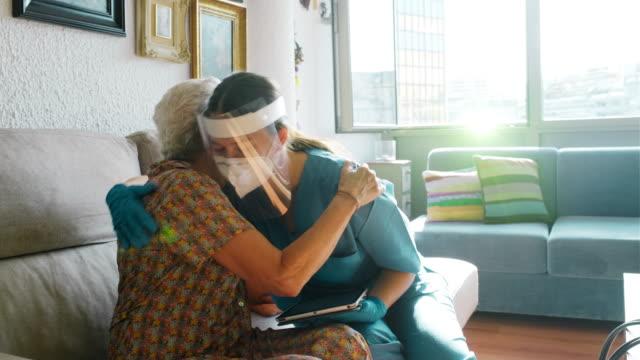 老婦人を慰め、covid調査を行う看護師。 - 老人ホーム点の映像素材/bロール