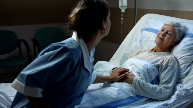 HD: Nurse Comforting Her Seriously Ill Patient HD1080p: Female nurse comforting seriously ill senior woman lying in bed in the middle of night in the hospital. cancer patient stock videos & royalty-free footage