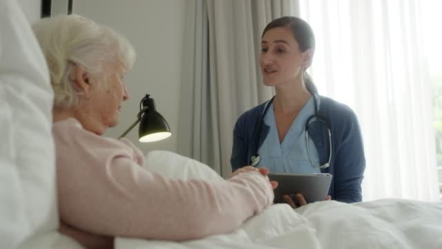 vídeos de stock e filmes b-roll de nurse discussing medical record with old woman - enfermeira