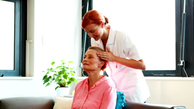 Nurse doing facial massage to her senior patient video