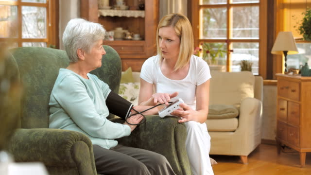 Nurse explaining blood pressure measuring to senior woman at home video