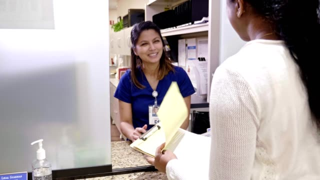 Nurse explains medical document to patient in doctor's office Mid adult nurse explains medical release forms to a female patient in a doctor's office. The nurse shows the patient where she needs to sign on the document. form filling stock videos & royalty-free footage