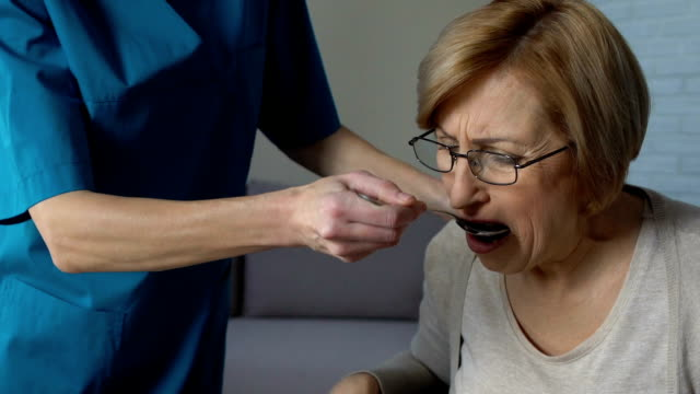 Nurse feeding disabled woman at home wiping with napkin, helplessness in old age Nurse feeding disabled woman at home wiping with napkin, helplessness in old age feeding stock videos & royalty-free footage