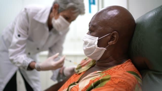 vidéos et rushes de infirmière donnant un projectile de vaccination à un patient - vaccin covid