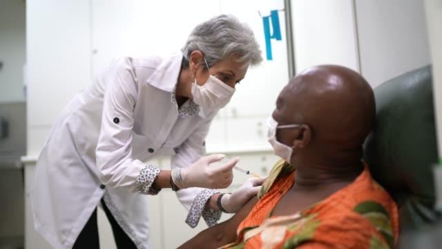 vídeos y material grabado en eventos de stock de enfermera que le da una vacunación a un paciente - vaccine