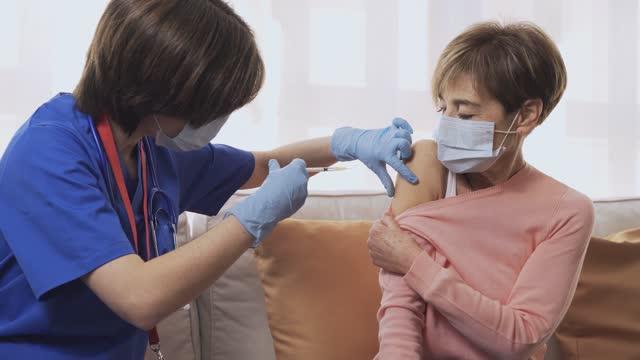 infermiera che dà il vaccino contro il coronavirus alla donna anziana all'interno di casa durante l'isolamento del blocco - iniezione covid-19 al concetto di paziente - focus sulla mano - braccio video stock e b–roll