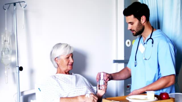 vidéos et rushes de infirmière lui donner des médicaments à un patient senior féminin - infirmier