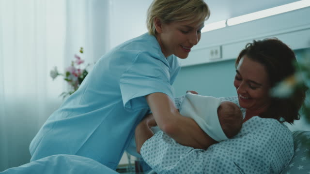sjuksköterska ger nyfödda barnet till mamma på sjukhuset - hålla bildbanksvideor och videomaterial från bakom kulisserna