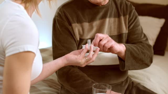 TU Nurse giving pill to senior man sitting on bed video