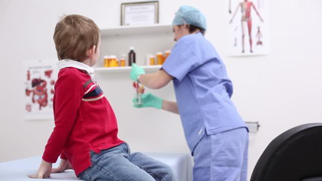 nurse giving young boy lollipop - 波板糖 個影片檔及 b 捲影像