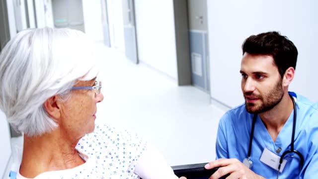 vidéos et rushes de infirmière, avoir une conversation avec le patient senior féminin - infirmier