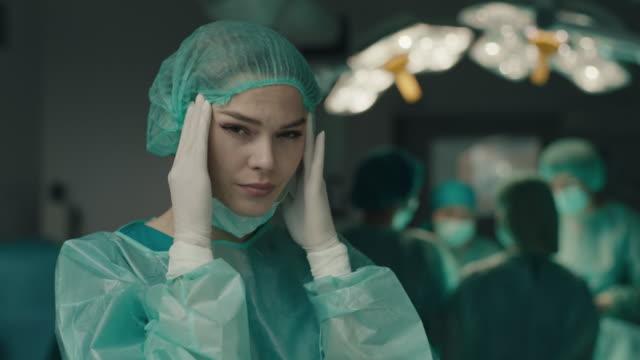ameliyathanede baş ağrısı olan hemşire - burnout stok videoları ve detay görüntü çekimi
