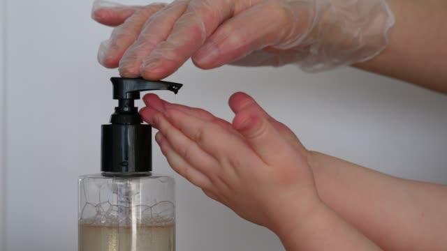 vidéos et rushes de infirmière aider peu de patient avec distributeur de savon liquide, plan rapproché - étudiant(e)