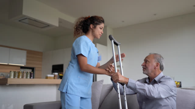 Nurse helping a senior amputee patient at home Female nurse helping a senior amputee patient at home crutch stock videos & royalty-free footage