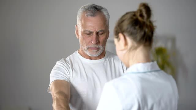 vídeos de stock e filmes b-roll de nurse helping old man to lift dumbbell, cardiac rehabilitation, injury recovery - coração fraco