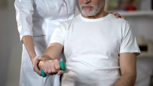 vídeos de stock e filmes b-roll de nurse helping pensioner to lift dumbbell, rehabilitation center after insult - coração fraco