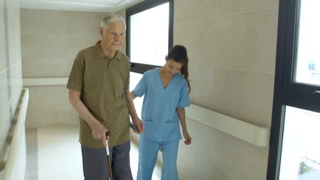 nurse helping senior man in using cane video