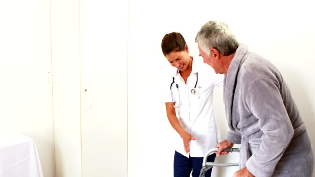 Nurse helping senior man to walk video