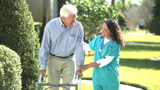 看護師支援シニア男屋外歩行器を使用 ビデオ