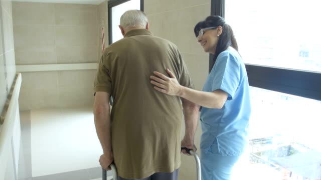 Nurse helping senior patient in using mobility walker video