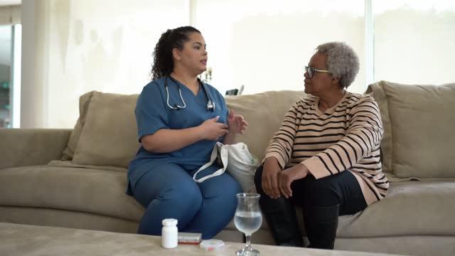 Nurse helping senior woman taking medicines at home