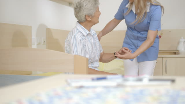 HD DOLLY: Nurse Helping Senior Woman To Stand Up video