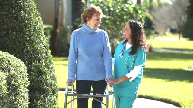 krankenschwester helfen senior frau mit einer gehhilfe im freien - geduld stock-videos und b-roll-filmmaterial