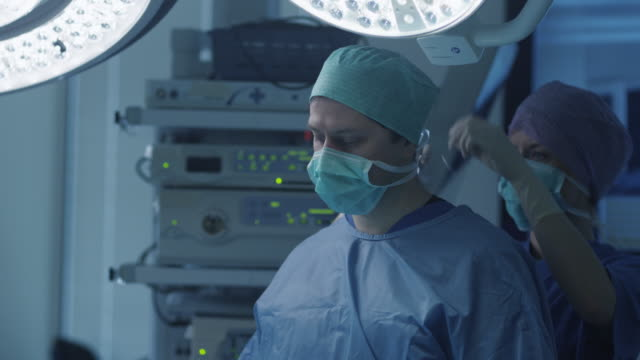 nurse helping to put surgical mask on doctor. - guanto indumento sportivo protettivo video stock e b–roll