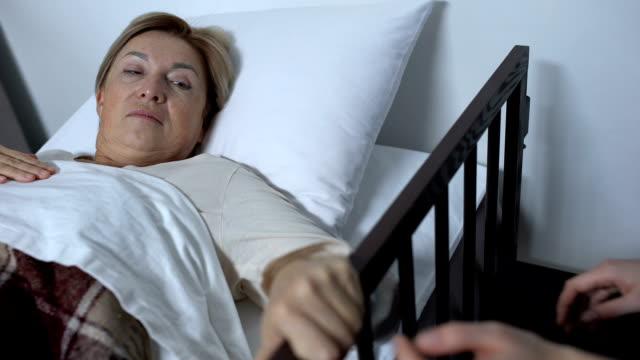 vídeos de stock, filmes e b-roll de enfermeira que ajuda o paciente maduro fraco da senhora para começ acima o sickbed, indo aos procedimentos - geriatria
