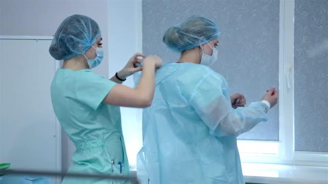 vídeos de stock e filmes b-roll de a nurse helps a senior nurse put on a surgical gown. - enfermeira