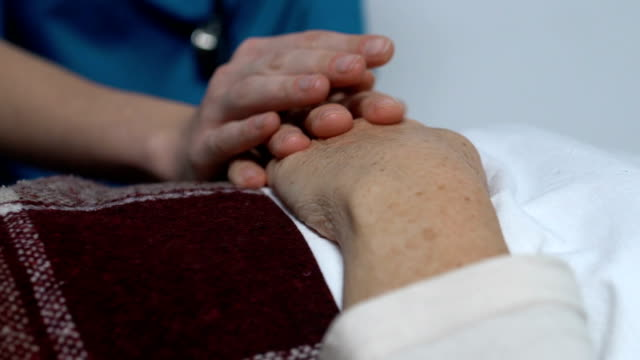 vídeos y material grabado en eventos de stock de enfermera sosteniendo mujer paciente acostado en la cama, sufriendo de enfermedad incurable - geriatría