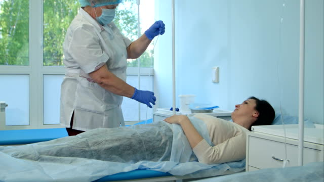 Nurse in gloves and mask putting female patient on a drip in a hospital ward video