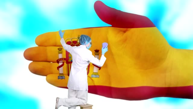 Nurse in medical mask and gloves washes large hand, painted in colors of Spain flag. State care for nation health. Wash your hands concept. Viruses protection. Diseases prevention - vídeo