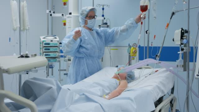 ds sjuksköterska i intensivvården ger en infusion till barn - intensivvårdsavdelning bildbanksvideor och videomaterial från bakom kulisserna