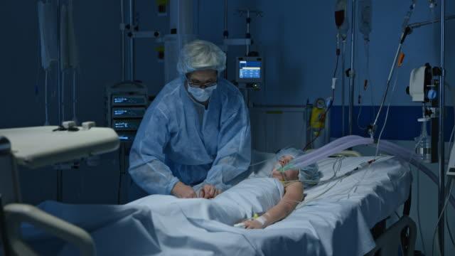 ds sjuksköterska på en intensivvårdsavdelning att ge ett barn en infusion - intensivvårdsavdelning bildbanksvideor och videomaterial från bakom kulisserna