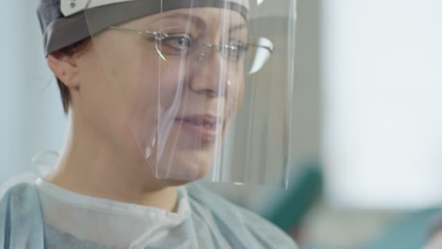 Nurse Labeling Test Tube Tilt down of mid-aged nurse in medical face shield smiling and holding test tube shield stock videos & royalty-free footage